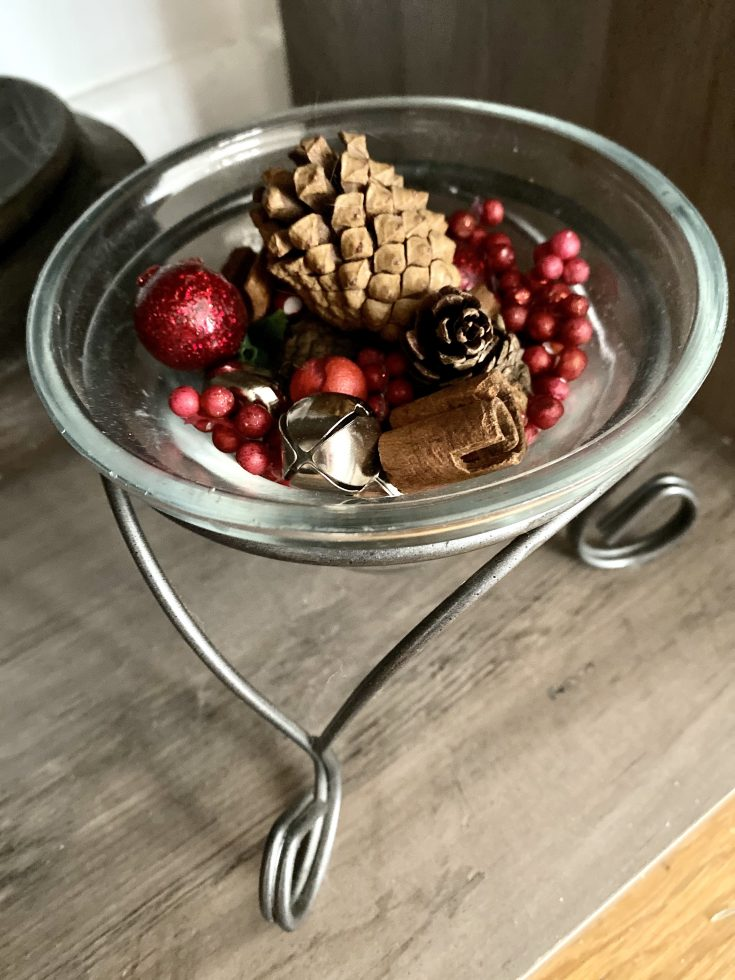 Rustic farmhouse glass bowl on stand with pine cones, fauw berries, cinnamon and jingle bells - perfect easy and cheap Christmas decor idea!