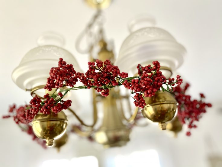 Berry garland hung on light fixture chandelier- perfect easy and cheap Christmas decor idea!
