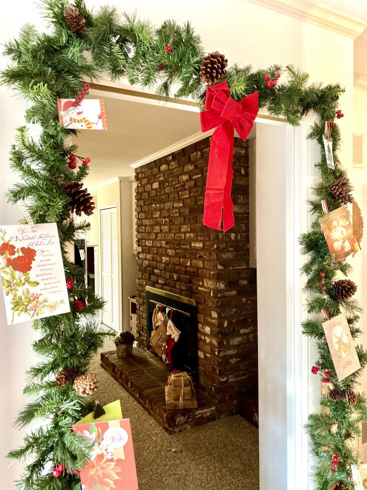 Rustic farmhouse doorway with garland with pines and berries and Christmas cards attached - perfect easy and cheap Christmas decor idea!
