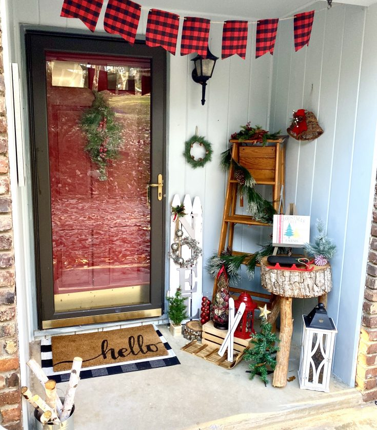 rustic Christmas porch with buffalo check banner, farmhouse signs, winter greens