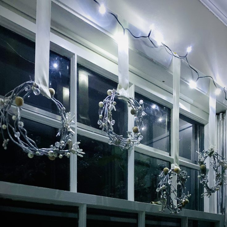 Rustic farmhouse icicle wreaths on ribbon hanging from windows with white twinkle lights - perfect easy and cheap Christmas decor idea!