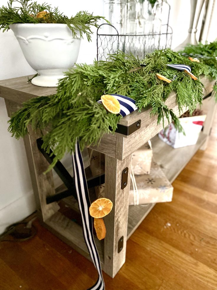 Evergreen cedar garland with navy striped ribbon and dried oranged, styled on rustic bench with cream bowl filled with greens - perfect easy and cheap Christmas decor idea!