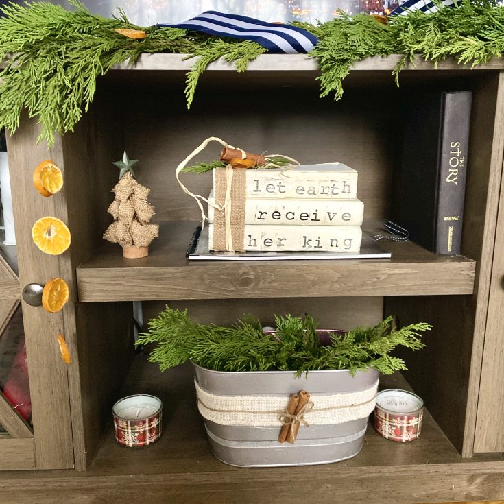 Rustic farmhouse shelf display with stamped books, galvanized pail with evergreens and cinnamon, evergreen garland with ribbon and dried oranges - perfect easy and cheap Christmas decor idea!