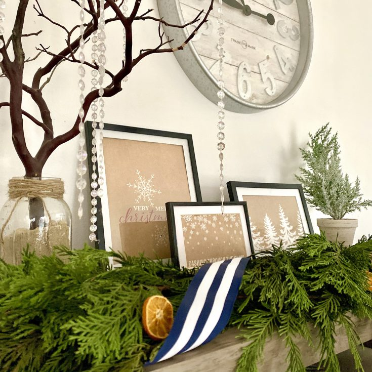 Rustic farmhouse tabletop with butcher paper gift bag Christmas prints in frames with evergreen garland, ribbon and dried oranges -perfect easy and cheap Christmas decor idea!
