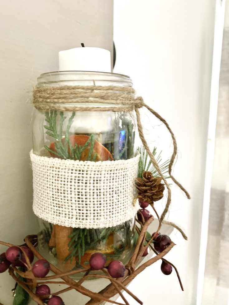 DIY jar with votive candle, filled with pine sprigs, dried oranges, cinnamon, with berry garland at base, wrapped in burlap ribbon with pine cone and pine branch atached -perfect easy and cheap Christmas decor idea!