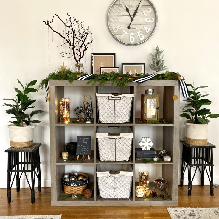 Rustic farmhouse style cube cabinet with Christmas decor, evergreen garland, lights - perfect easy and cheap Christmas decor idea!