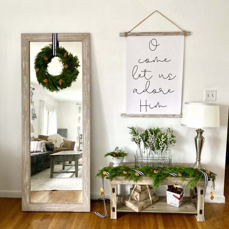 Rustic farmhouse mirror with DIY evergreen garland with orange slices, O Come Let Us Adore Him scroll frame print, rustic bench with evergreens, white berries, orange slices and ribbons  - perfect easy and cheap Christmas decor idea!