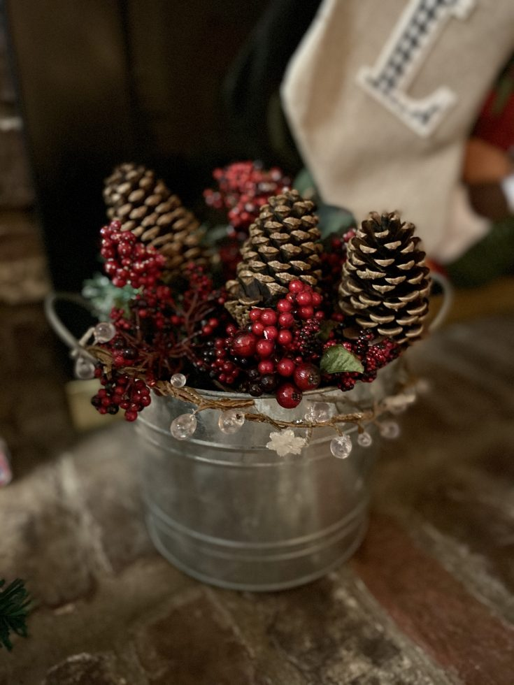Galvanized bucket with pine cones, berries, greens, and snowflake garland - perfect easy and cheap Christmas decor idea!