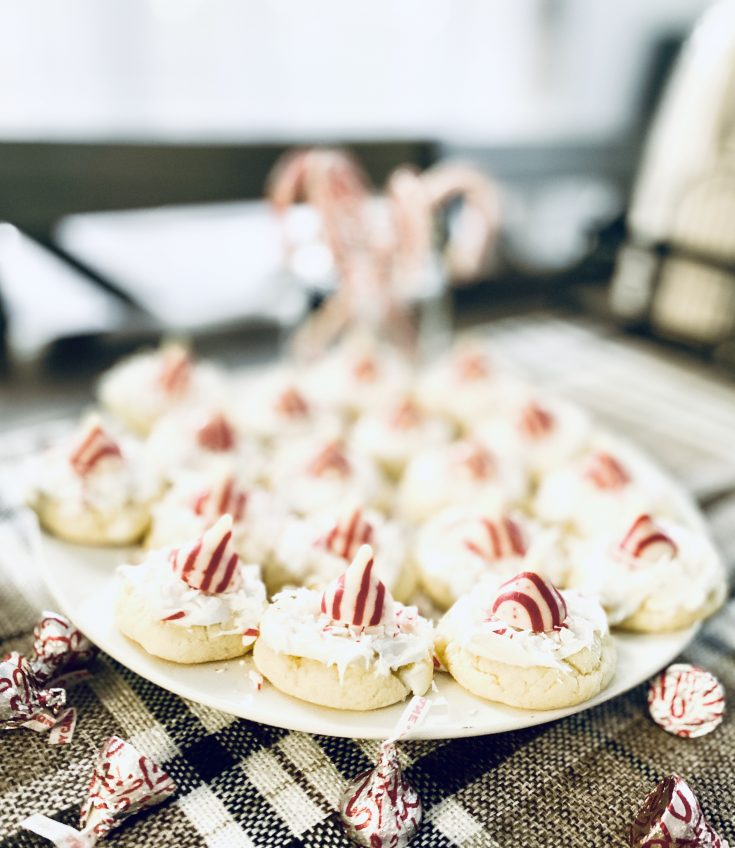 close up of north pole cake mix Christmas cookie - cookie with Hershey's Candy Cane Hug on top of white cake mix cookie, with white frosting, coconut, candy cane bits - easy Christmas cookie recipe!