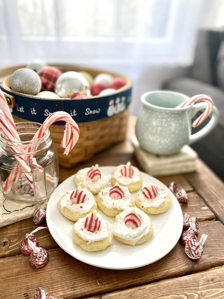 Hersheys Candy Cane Hugs on top of white cake mix cookies, with white frosting, coconut, candy cane bits, plated with jar of a candy canes, Christmas coffee mug with candy cane, basket of ornaments