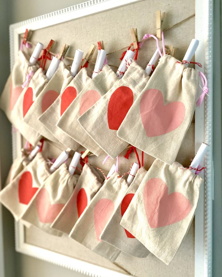 Valentine's DAy Countdown burlap heart treat sacks from Dollar Tree with rolled paper Acts of Kindness inside, hung on twine with clothespins on Hobby Lobby bulletin board