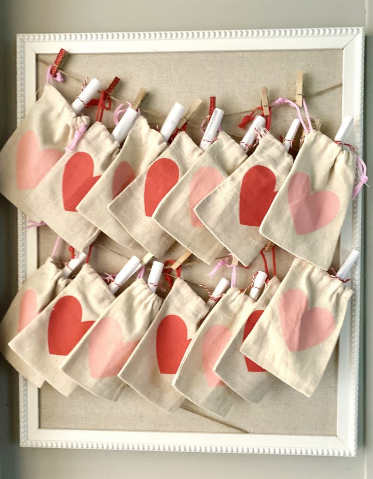 Hobby Lobby string bulletin board with burlap Dollar Tree heart treat sacks, hung with clothespines for Valentine's Day countdown and Acts of Kindness