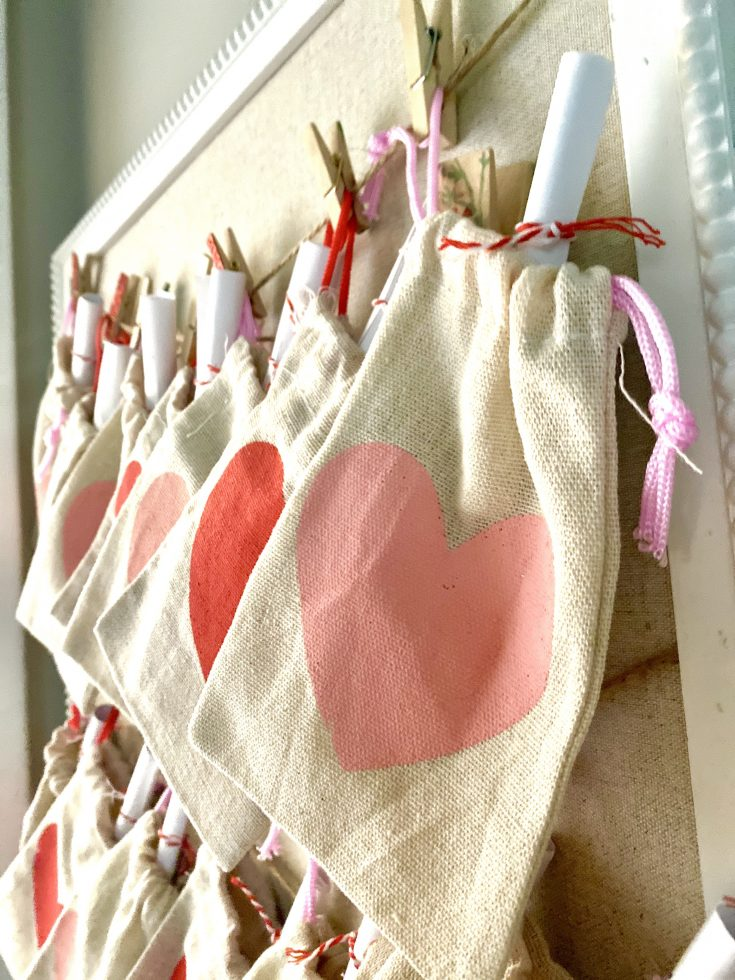 Close up of Dollar Tree burlap heart sack for Valetine's Day Acts of Kindness for kids, hung on bulletin board with twine and clothespins
